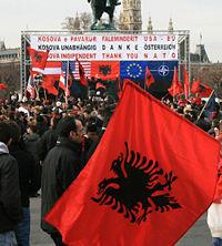 kosovares-celebrando-su-independencia-con-la-bandera-de-albania-flanqueada-por-la-europea-estadounidense-otan-y-austriaca
