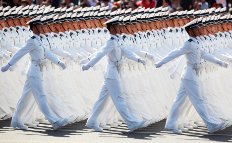 PLA sailors in white uniforms march past Tiananmen Square during the celebration of China's 60th anniversary on October 1, 2009 in Beijing, China. (Feng Li/Getty Images)