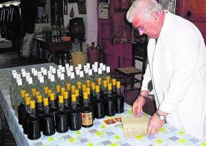 Juan Juan Micó hojea, junto a licores recién embotellados, el libro de sus fórmulas secretas, que guarda en una caja fuerte. :: V LLADRÓ