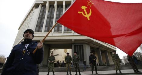 Un hombre sosyiene una bandera de la Unión Soviética ante el edificio del Parlamento de Crimea. (Reuters)