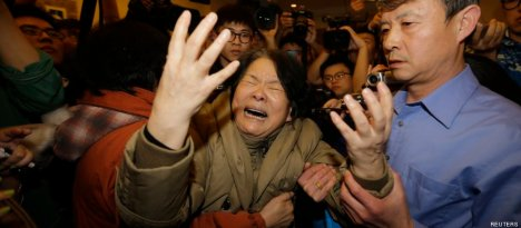 A family member of a passenger aboard Malaysia Airlines MH370 cries as she is surrounded by journalists after watching a television broadcast of a news conference, at the Lido hotel in Beijing