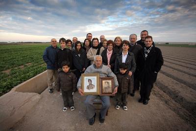 Matías Gimeno Orts, rodeado por familiares de Juan Bautista García Sales, sostiene la foto de la víctima a la derecha y la suya, a la izquierda. / JESÚS CISCAR