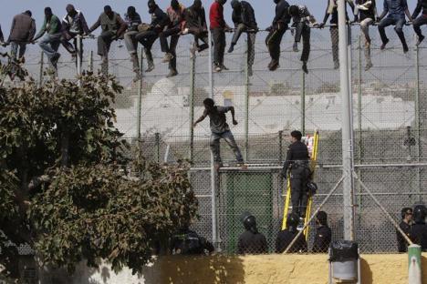 Varios de los inmigrantes de origen subsahariano que se encaramaron ayer a la valla de Melilla, en el momento en que comenzaron a bajar tras permanecer subidos alrededor de seis horas. / F. G. Guerrero (Efe)